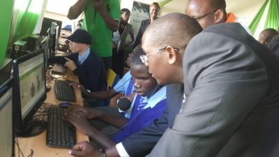 Safaricom's Director of Corporate Affairs Nzioka Waita takes Neslon, a student at Thika School for the Blind through the new Safaricom website